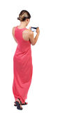Πίσω άποψη της μόνιμης νέας όμορφης γυναίκας που χρησιμοποιεί ένα κινητό pho Στοκ εικόνες με δικαίωμα ελεύθερης χρήσης