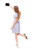 Πίσω άποψη της μόνιμης νέας όμορφης γυναίκας στη φανέλλα και χρησιμοποίηση Στοκ φωτογραφία με δικαίωμα ελεύθερης χρήσης