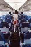 Πίσω άποψη της νέας γυναίκας που περπατά το διάδρομο στο αεροπλάνο στοκ φωτογραφίες