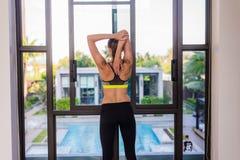 Πίσω άποψη της νέας γυναίκας που τεντώνει κάνοντας το πρωί workout στο θέρετρο ξενοδοχείων πολυτελείας με μια μεγάλη άποψη Θηλυκό Στοκ Εικόνες