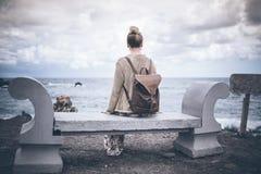 Πίσω άποψη της νέας γυναίκας στο μακρύ φόρεμα και με τη συνεδρίαση σακιδίων πλάτης στον πάγκο πετρών θαλασσίως Στοκ Φωτογραφίες