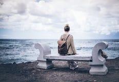 Πίσω άποψη της νέας γυναίκας στο μακρύ φόρεμα και με τη συνεδρίαση σακιδίων πλάτης στον πάγκο πετρών θαλασσίως Στοκ φωτογραφία με δικαίωμα ελεύθερης χρήσης