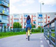Πίσω άποψη της νέας γυναίκας στο φόρεμα που οδηγά το εκλεκτής ποιότητας ποδήλατο Στοκ Φωτογραφία
