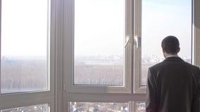 Πίσω άποψη της νέας επιτυχούς στάσης επιχειρηματιών μπροστά από τα παράθυρα που εξετάζουν την απόσταση στην πόλη o φιλμ μικρού μήκους