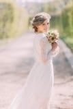 Πίσω άποψη της νέας ξανθής νύφης στο άσπρο φόρεμα με τη νυφική ανθοδέσμη που στέκεται υπαίθρια Στοκ Εικόνα