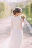 Πίσω άποψη της νέας ξανθής νύφης στο άσπρο φόρεμα που εξετάζει τη νυφική ανθοδέσμη υπαίθριας Στοκ Εικόνες