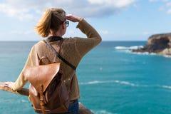 Πίσω άποψη της νέας ξανθής στάσης γυναικών στον απότομο βράχο επάνω από τον ωκεανό που προστατεύει τα μάτια της με το χέρι από το Στοκ φωτογραφίες με δικαίωμα ελεύθερης χρήσης
