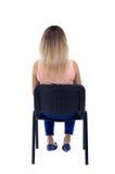 Πίσω άποψη της νέας όμορφης συνεδρίασης γυναικών στην καρέκλα Στοκ φωτογραφία με δικαίωμα ελεύθερης χρήσης