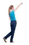 Πίσω άποψη της περπατώντας γυναίκας στα τζιν και την υπόδειξη πουκάμισων Στοκ φωτογραφία με δικαίωμα ελεύθερης χρήσης