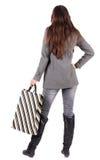 Πίσω άποψη της πηγαίνοντας γυναίκας στη γυναίκα παλτών με τις τσάντες αγορών Στοκ Φωτογραφία