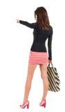 Πίσω άποψη της πηγαίνοντας γυναίκας στο φόρεμα με το pointin τσαντών αγορών Στοκ φωτογραφία με δικαίωμα ελεύθερης χρήσης
