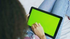 Πίσω άποψη της σγουρής γυναίκας στο σπίτι που χρησιμοποιεί την ηλεκτρονική ταμπλέτα με την πράσινη οθόνη απόθεμα βίντεο