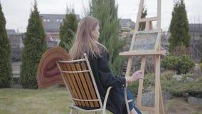 Πίσω άποψη της συνεδρίασης ζωγράφων νέων κοριτσιών μπροστά από ξύλινο easel που σύρει μια εικόνα και ένα κάπνισμα Θηλυκός καλλιτέ απόθεμα βίντεο