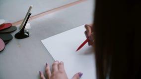 Πίσω άποψη της συνεδρίασης γυναικών στον πίνακα με το τακούνι και τα υφαντικά δείγματα σε το, σκίτσο σχεδίων σε χαρτί ολισθαίνων  απόθεμα βίντεο