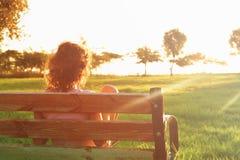 Πίσω άποψη της συνεδρίασης παιδιών στον πάγκο στο ηλιοβασίλεμα στο πάρκο Στοκ εικόνες με δικαίωμα ελεύθερης χρήσης