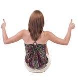 Πίσω άποψη της τοποθέτησης της νέας ξανθής γυναίκας που παρουσιάζει αντίχειρα Στοκ Εικόνες
