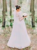 Πίσω άποψη της όμορφης νύφης στο μακρύ γαμήλιο φόρεμα που κρατά την ανθοδέσμη των peonies Δασική θέση Στοκ φωτογραφία με δικαίωμα ελεύθερης χρήσης
