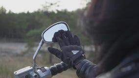 Πίσω άποψη της unrecognizable συνεδρίασης κοριτσιών στη μοτοσικλέτα που καθαρίζει τον καθρέφτη με το φορημένο γάντια χέρι της Τρί απόθεμα βίντεο