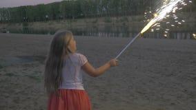 Πίσω άποψη του λίγο ξανθού τρεξίματος κοριτσιών σε μια παραλία και του κρατήματος των πυροτεχνημάτων φιλμ μικρού μήκους
