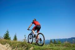 Πίσω άποψη του αθλητικού ποδηλάτη τουριστών στο κράνος και το πλήρες ποδήλατο ανακύκλωσης εξοπλισμού επάνω ο χλοώδης λόφος στοκ φωτογραφία