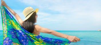 Πίσω άποψη του ασιατικού μαγιό ένδυσης γυναικών και των ανοιγμένων αγκαλών στην τροπική παραλία την ηλιόλουστη ημέρα με τον όμορφ στοκ φωτογραφία με δικαίωμα ελεύθερης χρήσης