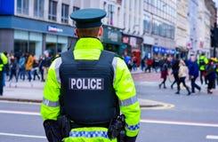 Πίσω άποψη του αστυνομικού σε έναν δρόμο με έντονη κίνηση στο κέντρο της πόλης του Μπέλφαστ Στοκ φωτογραφία με δικαίωμα ελεύθερης χρήσης