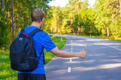 Πίσω άποψη του ατόμου που κάνει ωτοστόπ στο δασικό δρόμο Στοκ Φωτογραφία