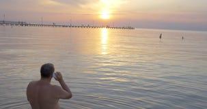 Πίσω άποψη του ατόμου που μιλά πέρα από το τηλέφωνο προσέχοντας το ηλιοβασίλεμα φιλμ μικρού μήκους