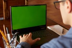 Πίσω άποψη του ατόμου freelancer στα γυαλιά που λειτουργούν με το lap-top πράσινη οθόνη Καυκάσιος επιχειρηματίας που κάνει το πρό Στοκ Φωτογραφία