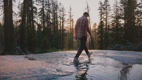 Πίσω άποψη του ελεύθερου νεαρού άνδρα που περπατεί στο μικρό ρεύμα νερού που απολαμβάνει καταπληκτικός το πεζοπορώ ηλιοβασιλέματο απόθεμα βίντεο