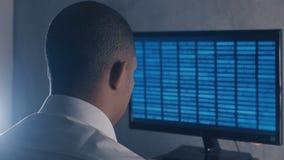 Πίσω άποψη του επαγγελματικού κώδικα προγραμματισμού προγραμματιστών στο γραφείο οργάνων ελέγχου υπολογιστών τη νύχτα απόθεμα βίντεο