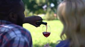 Πίσω άποψη του ευτυχούς χύνοντας κρασιού ζευγών στο γυαλί, επέτειος εορτασμού υπαίθρια φιλμ μικρού μήκους