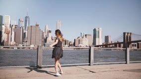 Πίσω άποψη του κοριτσιού με την τρίχα που φυσά στον αέρα που περιστρέφει στην όμορφη άποψη οριζόντων του Μανχάταν, ανοικτός σε αρ απόθεμα βίντεο