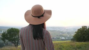 Πίσω άποψη του λατρευτού νέου κοριτσιού με το καπέλο φιλμ μικρού μήκους