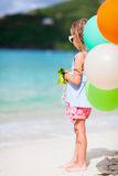 Πίσω άποψη του μικρού κοριτσιού με τα μπαλόνια στην παραλία Στοκ Φωτογραφίες