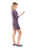 Πίσω άποψη του μόνιμου νέου όμορφου κοριτσιού με τον υπολογιστή ταμπλετών Στοκ φωτογραφία με δικαίωμα ελεύθερης χρήσης