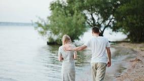 Πίσω άποψη του νέου ελκυστικού ζεύγους που περπατά στην ακτή της λίμνης το βράδυ στο ηλιοβασίλεμα Άνδρας και γυναίκα στην παραλία απόθεμα βίντεο