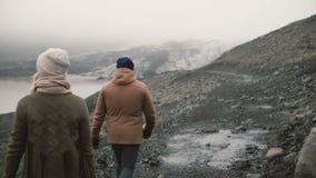 Πίσω άποψη του νέου ζεύγους που περπατά στη λιμνοθάλασσα πάγου Άνδρας και γυναίκα που στα βουνά στην Ισλανδία από κοινού απόθεμα βίντεο
