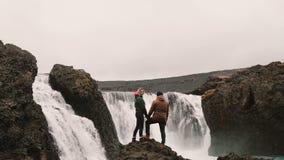 Πίσω άποψη του νέου ζεύγους που στέκεται σε έναν βράχο και που κοιτάζει σε έναν ισχυρό καταρράκτη στην Ισλανδία, που κρατά τα χέρ φιλμ μικρού μήκους