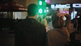 Πίσω άποψη του νέου ζεύγους hipster που στέκεται στο κέντρο της πόλης και που ακούει η συναυλία, απόδοση μουσικών το βράδυ απόθεμα βίντεο