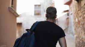 Πίσω άποψη του νεαρού άνδρα που περπατά στην οδό πόλεων στην Ευρώπη στο πρωί Άτομο που εξερευνά την παλαιά πόλη μόνη, κοιτάζοντας απόθεμα βίντεο