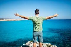 Πίσω άποψη του νεαρού άνδρα που αυξάνει τα χέρια του πάνω από τον απότομο βράχο επάνω από το β Στοκ φωτογραφία με δικαίωμα ελεύθερης χρήσης