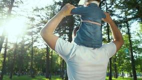 Πίσω άποψη του παιχνιδιού πατέρων με το κοριτσάκι του στους ώμους στη φλόγα φακών πάρκων φιλμ μικρού μήκους