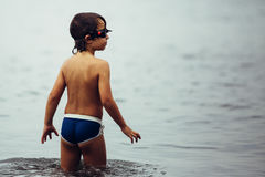 Πίσω άποψη του παιδιού στους κορμούς και των προστατευτικών διόπτρων στη θάλασσα Στοκ εικόνα με δικαίωμα ελεύθερης χρήσης