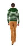 Πίσω άποψη του πηγαίνοντας όμορφου ατόμου στα τζιν και το ριγωτό πουλόβερ Στοκ Εικόνες