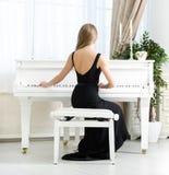 Πίσω άποψη του πιάνου συνεδρίασης και παιχνιδιού μουσικών στοκ εικόνες