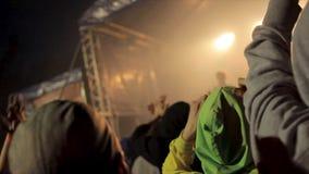 Πίσω άποψη του πλήθους των ανθρώπων στη συναυλία footage Σκιαγραφίες του πλήθους συναυλίας μπροστά από τα φωτεινά φω'τα σκηνών Στοκ Εικόνες