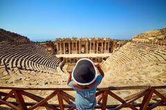Πίσω άποψη του ταξιδιώτη γυναικών στο καπέλο που εξετάζει τις καταπληκτικές καταστροφές αμφιθεάτρων σε αρχαίο Hierapolis, Pamukka στοκ εικόνες με δικαίωμα ελεύθερης χρήσης