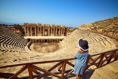 Πίσω άποψη του ταξιδιώτη γυναικών στο καπέλο που εξετάζει τις καταπληκτικές καταστροφές αμφιθεάτρων σε αρχαίο Hierapolis, Pamukka στοκ εικόνες