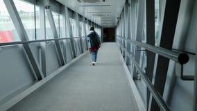Πίσω άποψη του τουρίστα γυναικών που επιβιβάζεται στο αεροπλάνο που περπατά μέσω της γέφυρας πυλών στο τερματικό αερολιμένων r φιλμ μικρού μήκους